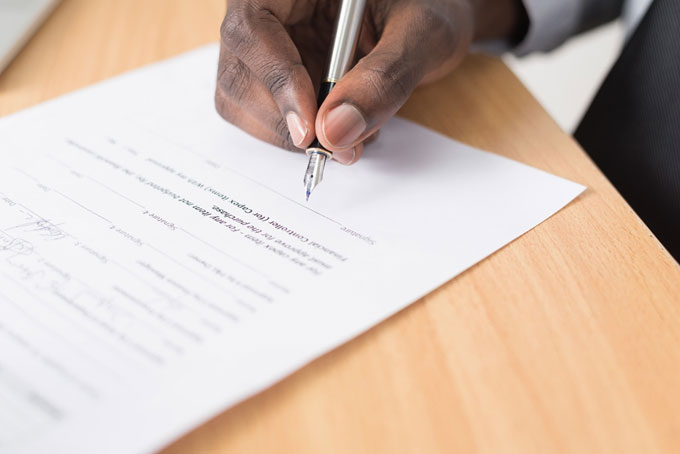 A hand signing a contract on the dotted line with a fountain pen.
