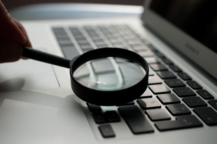 A magnifying glass held to a laptop keyboard